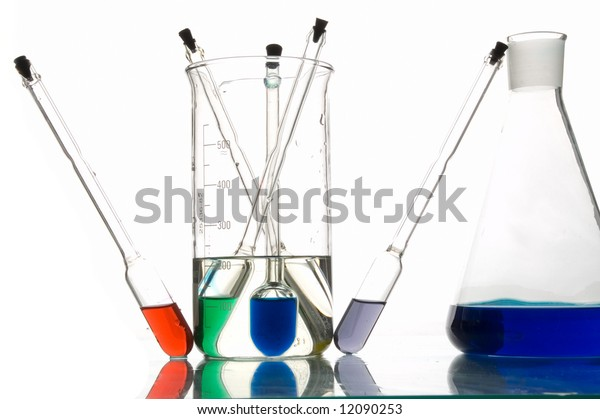 red, blue and green retorts with liquids, white background, close-up