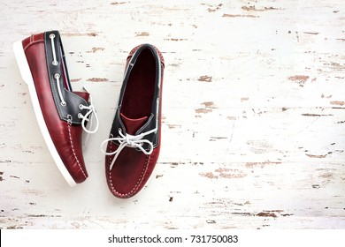 Red and blue leather men's top sider shoes or boat shoes on a white wooden board. Fashion advertising shoes photos.