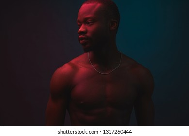 Red and blue lighted portrait of young and sexy muscular shirtless man with neck chain. Flat shadows