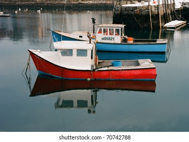 Red and Blue Lobster boats moored in calm, reflective harbor