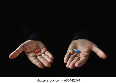 Red and blue pills on hand isolated on black background
