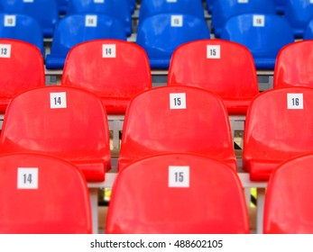 Red and blue plastic armchairs on stadium
