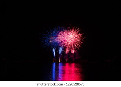 Red and blue rich stars from fireworks over surface of Brno's Dam with reflection on the surface of lake