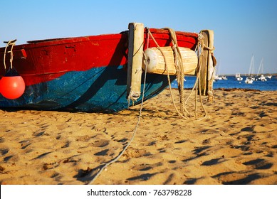 A red and blue small fishing boat, a remnant of Cape Cod's immigrant fishing traditions, lays stranded on a beach at low tide