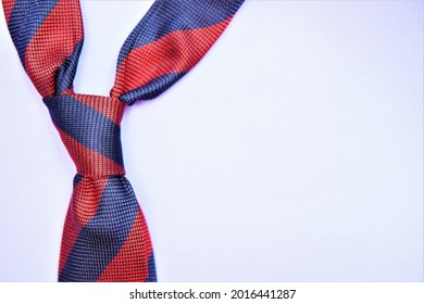 A red and blue striped tie tied on a solid purple background. Four in hand knot