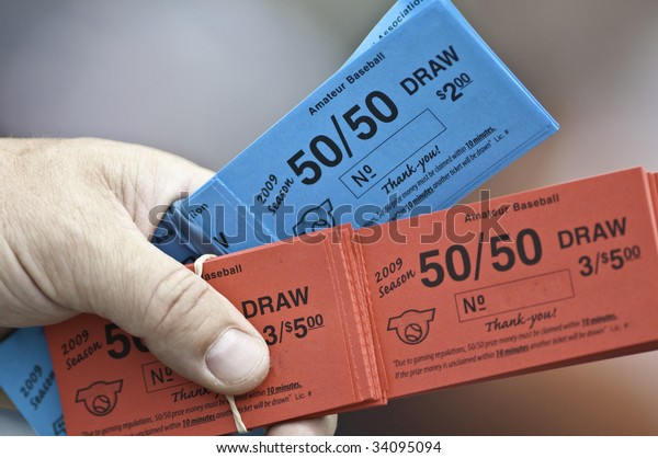 Red and blue tickets for a 50/50 draw.Partial hand and fingers hold the tickets,