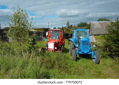 red and blue tractor are in the yard, two tractors in a village near the wood house