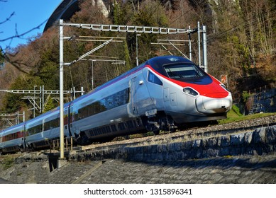 Red blue train in motion alps mountains. High speed mountain train arrives at Switzerland train station in mountains