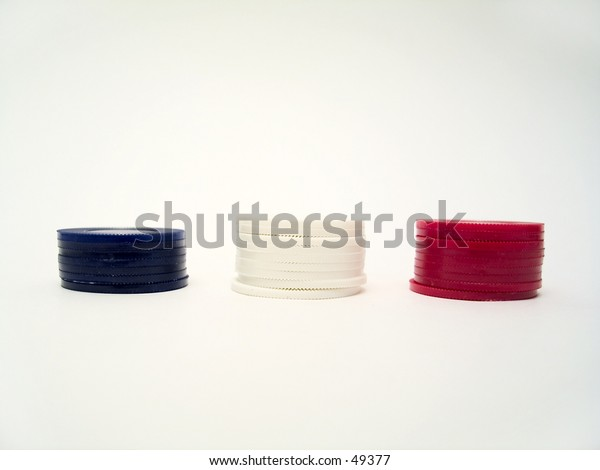 Red, blue and white poker chips stacked together on a white background.