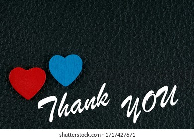 red and blue wooden hearts with thank you phrase on black leather