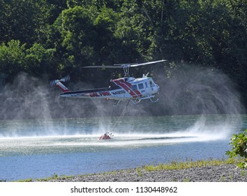 Red Bluff, California, USA - 23 June 2018: a CalFire Helicopter Loads Water from the Sacramento River to Fight a Wildfire Nearby Red Bluff.
