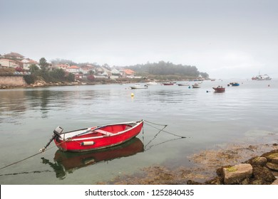 Red boat anchored on Naval fishing port in Arousa island under the morning mist