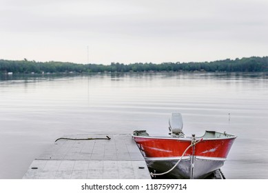 Red boat isolated on quiet lake on overcast day