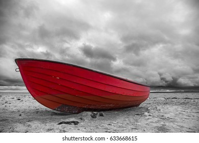 Red boat laying on the sandy beach at stormy weather