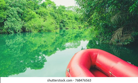 Red boat on the river. River with green water, beautiful nature landscape. Red inflatable boat for adventurers and ride of tourists on Formoso river in Bonito MS, Brazil.