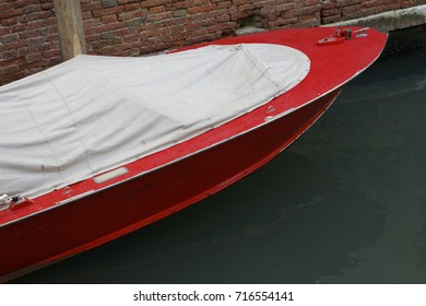 red boat with white cover on green water in venice italy