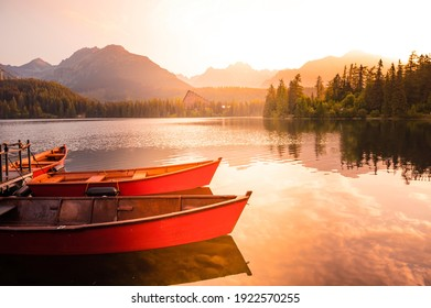 Red boats on Lake Strbske pleso. Morning view of the High Tatras National Park, Slovakia, Europe.