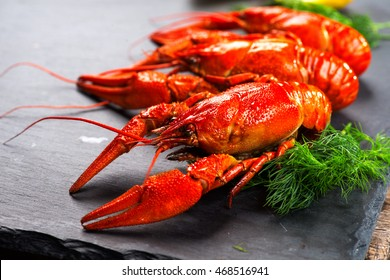 Red boiled crayfish or crawfish with lemon and herbs on stone slate dark background.  Lobster closeup