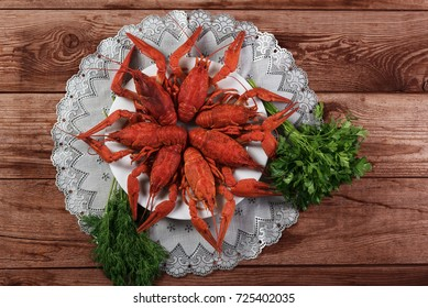 Red boiled crayfish with dill on wooden background