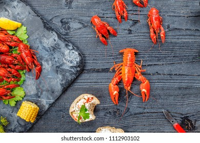 Red boiled crayfish with lemon, corn and parsley on stone slate tray on dark old rustic background