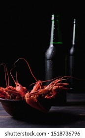 Red boiled crayfish in a plate and cold beer in bottles. Great beer snack.
