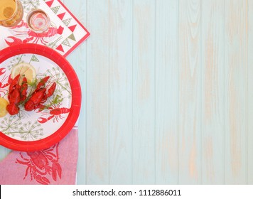 Red boiled crayfish with twig of dill on the white plate, wooden rustic table . Two snaps glass of liquor with salt on edge, white vine. Traditional Finnish Crawfish fest, napkin crawfish