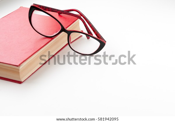 Red book and glasses on a light background
