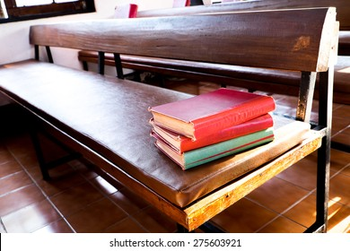 Red books stack on wooden bench. The red books are the old songbook in church.