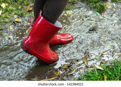 Red boots in the water.