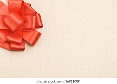 Red bow on cardboard background