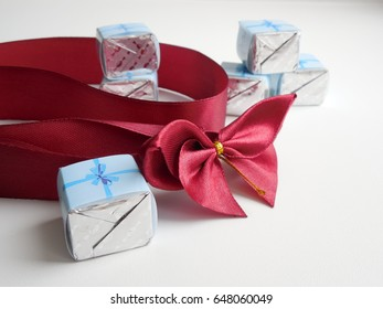 Red bow with red ribbon and candy in the shape of a cube
