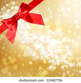 Red Bow and Ribbon with Gold Bokeh Lights Background