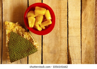 Red bowl with jackfruit pods and jackfruit skin, top view