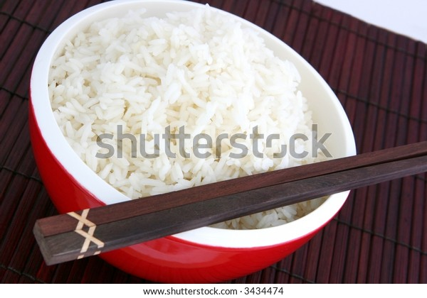 Red bowl of white rice, with chopsticks.  On a bamboo placemat.
