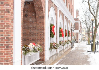 Red bows adorn wreaths hanging in the windows on a quiet, snowy, small-town Mainstreet, Hanover, New Hampshire.