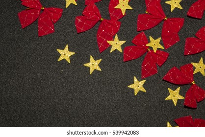 Red bows and yellow gold stars on black background with copy space