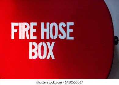 Red box with Fire Hose Box inscription, ferry safety equipment. Abstract photo of vessel safety appliance. Fire prevention and protection. Public place firefighting tool. Red sign of firehose storage