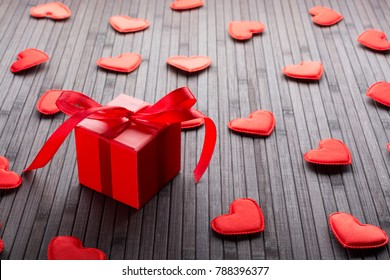Red box with gift and figurines of hearts on the table