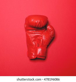 Red boxing glove on red background - Flat lay