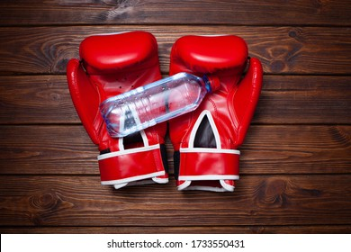 Red boxing gloves with bottle of water on wooden background