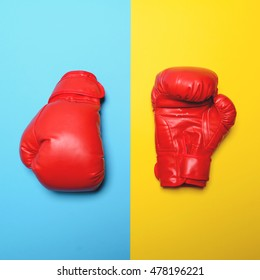 Red boxing gloves on blue and yellow background - Flat lay