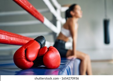 Red boxing gloves on boxing ring in gym. Sports equipment for training