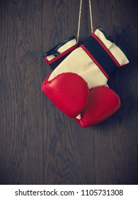 Red boxing gloves on a rustic wooden wall, sports or assertiveness concept