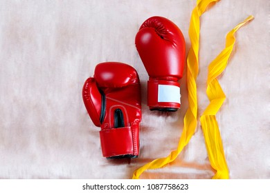 Red boxing gloves and yellow polyester wraps for muay thai or accessories kickboxing supporting your joint of hands on nude satin background