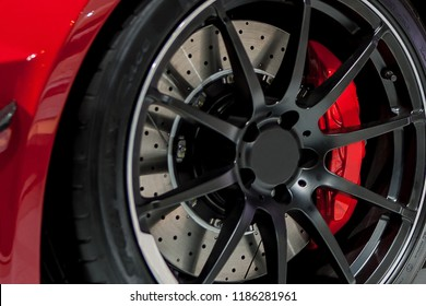Red Brake Calipers On Red Car With Black Rims