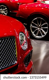 Red brand new luxury cars displayed at auto show dealer booth