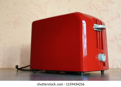 Red bread toaster on grey grunge table with copy space for text. Kitchen equipment concept.