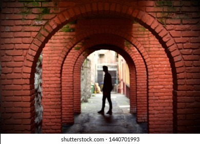 Red brick alleyway with a human silhouette at the opening