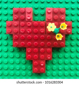 Red Brick block was set up to be in a heart shape on the green background decorated with yellow flower for lover on valentine's day