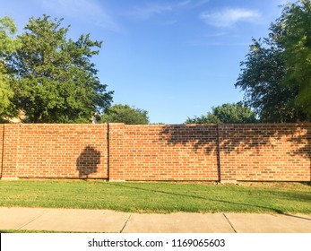 Red brick block wall function as barrier between neighborhood and public right-of-way. Screen walls and sound walls, fencing system separate subdivisions from busy streets with pedestrian pathway